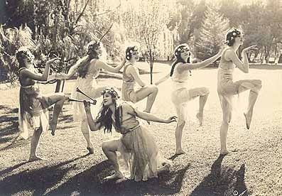 Group of women in gauzy, Grecian costumes dancing
