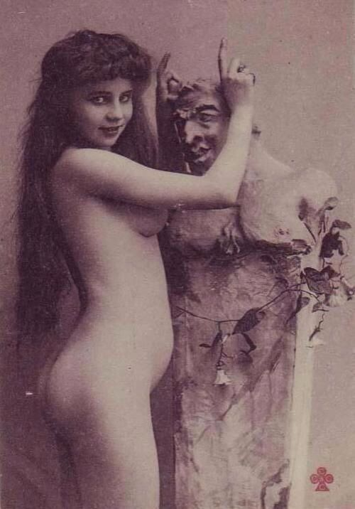 Nude Victorian woman standing in front of a bust of a devil-like figure
