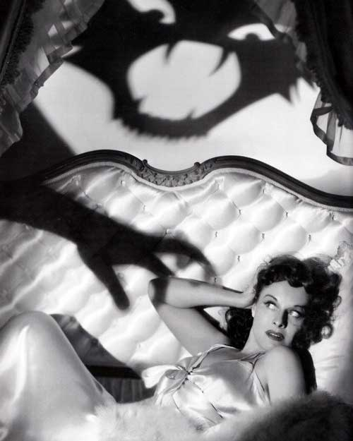 a woman in a nightgown with a shadow monster above her