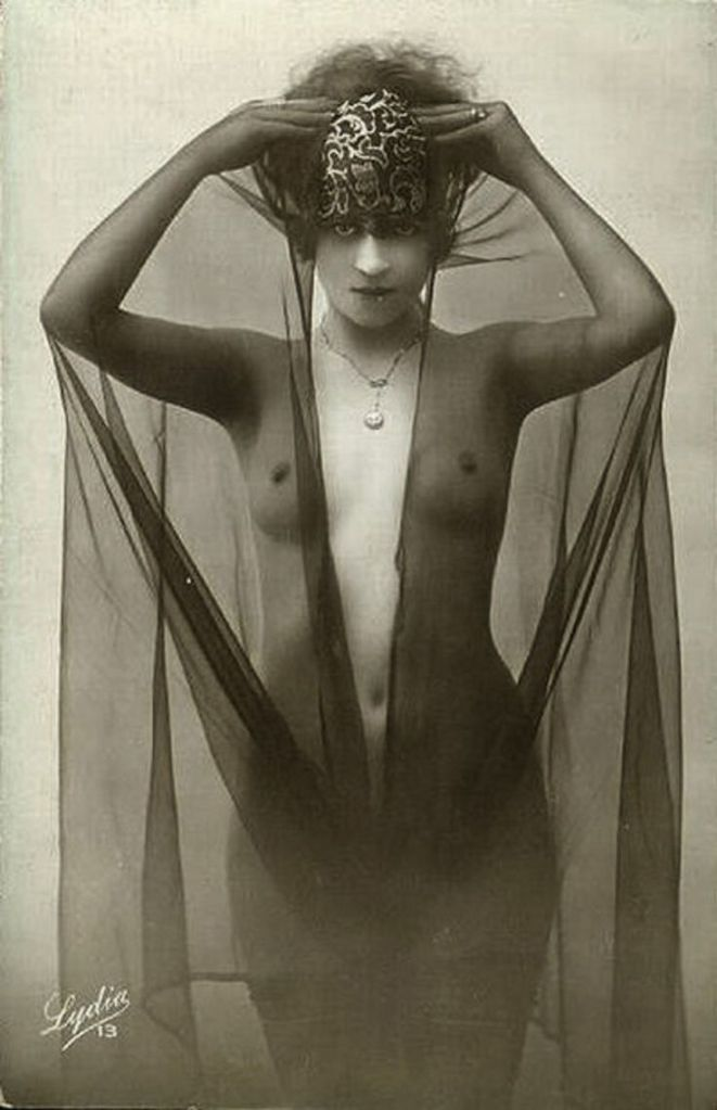 Nude woman wearing a crown and swathed in black veil
