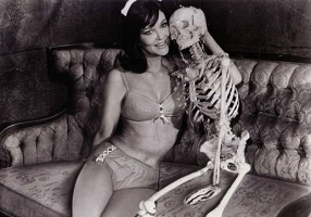 woman in lingerie sitting with a skeleton