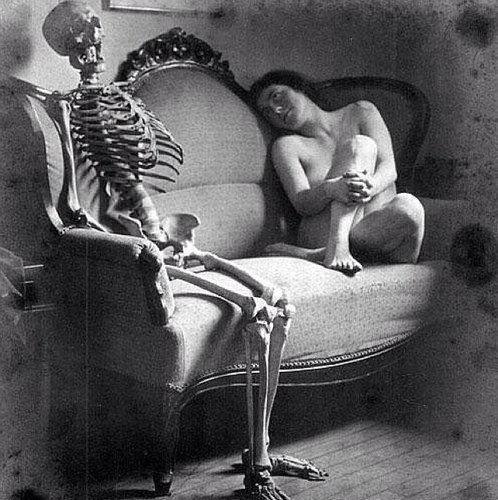 a nude woman looking lovingly at a skeleton