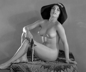 Nude seated woman wearing  a pirate hat and holding a pistol