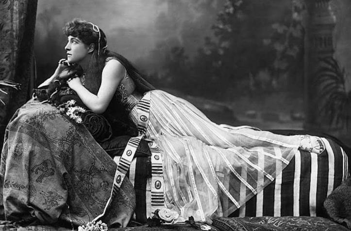 """Victorian woman wearing a """"harem"""" costume, reclining on a sofa"""