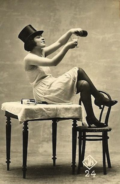 victorian woman seated on a table wearing a slip and top hat pouring champagne