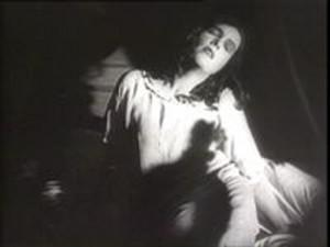 woman in a nightgown with the shadow of a hand on her chest