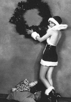 silent film pinup hanging a wreath  wearing a backless santa dress