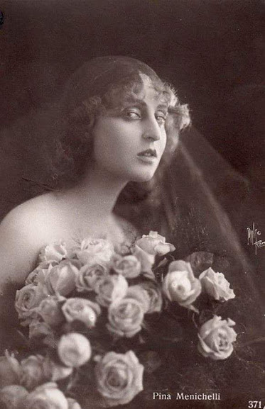 black and white photo of a woman wearing a veil and carrying roses