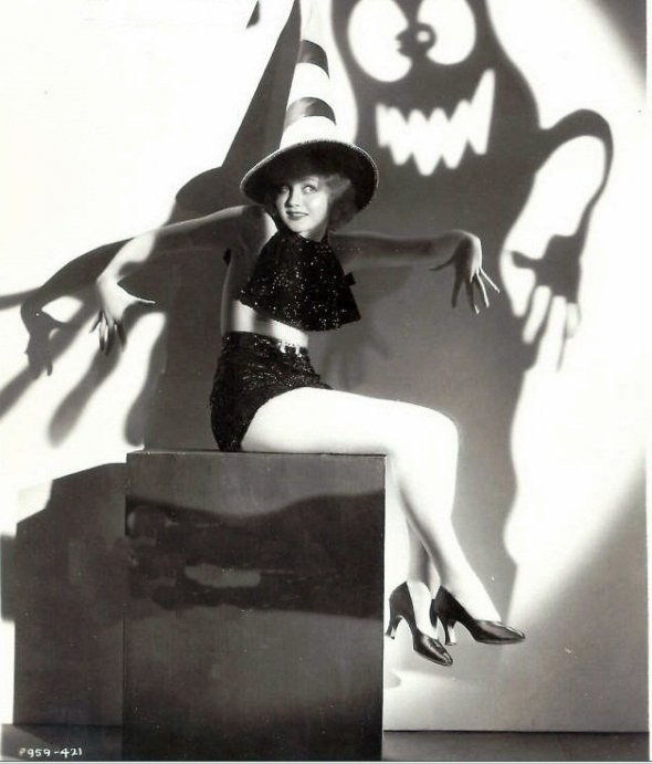 Flapper in a a witch's hat with a ghostly shadow behind her