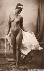 Nude woman of African decent. Standing, wearing 2 strings of pearls and a bow in her hair