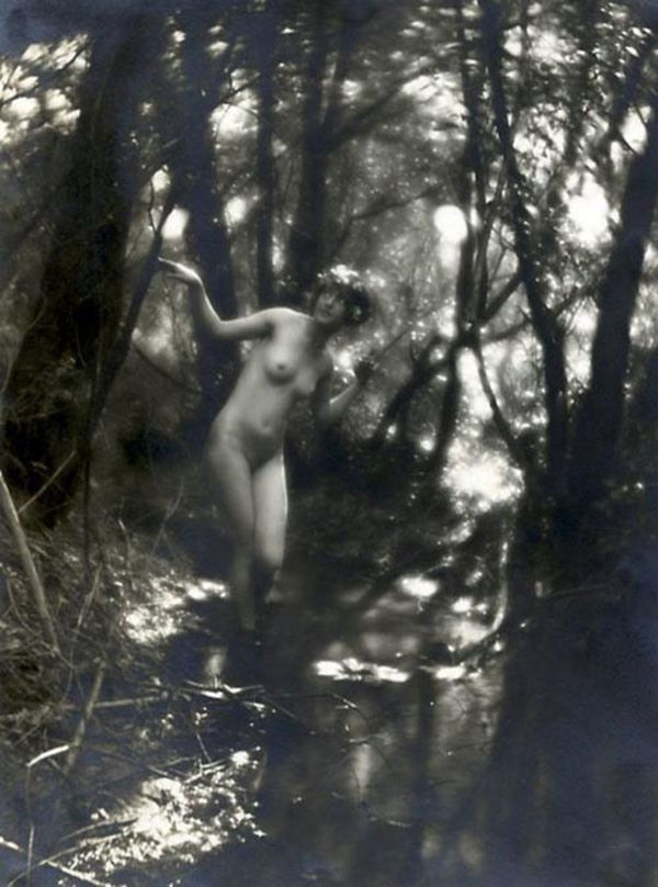 Nude woman wearing a flower crown in the woods.