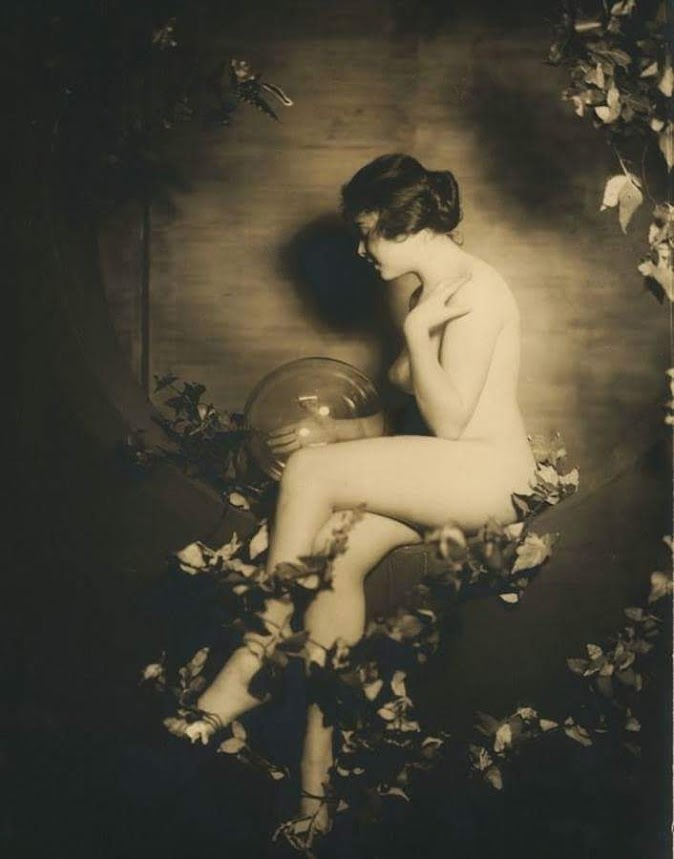 Nude woman in profile. Seated surrounded by flowers, holding a glass orb.