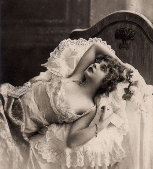 Edwardian woman wearing a chemise reclining in bed