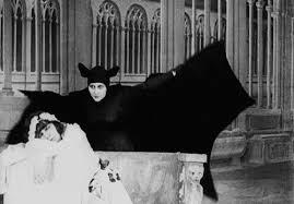 Woman in vampire bat costume looming over a sleeping woman