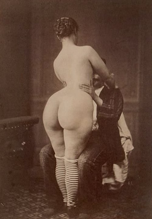 Nude woman standing in front of a clothed man