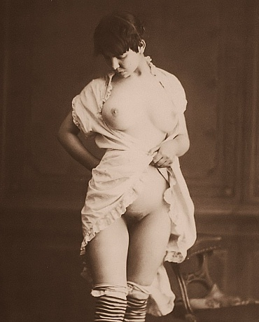 Victorian woman in striped stockings and chemise revealing her breasts and vulva