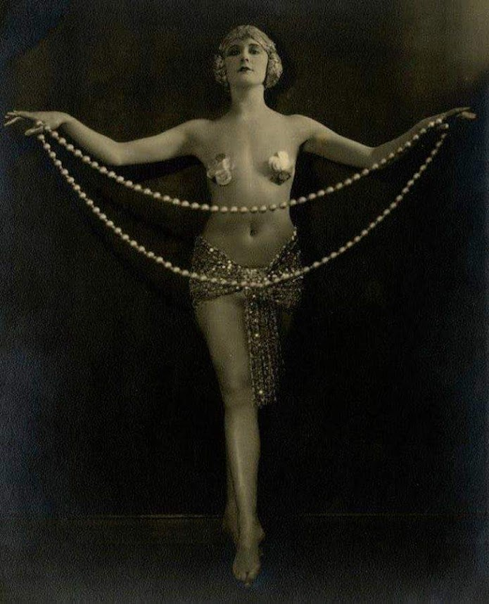 woman wearing a golden headdress, gold pasties, an a gold loincloth. She holds a long rope of beads