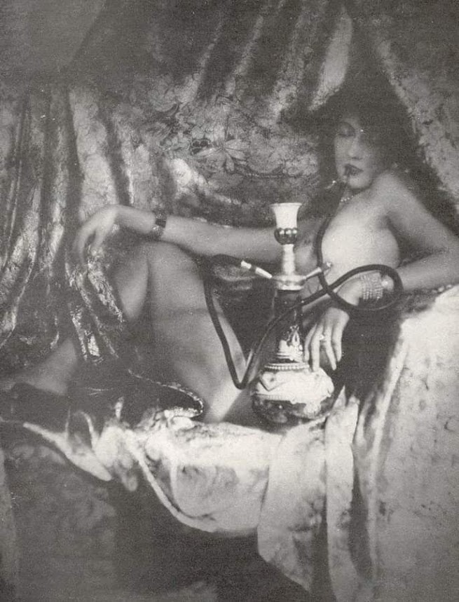 seated nude woman with dark hair and a hookah pipe
