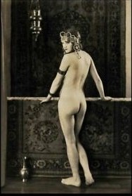 Nude woman with her back to the camera. Wearing ancient Egyptian style headdress.  Circa 1920s