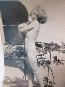 Nude, blond woman standing covering her breasts with her arms. She is outside surrounded by plants. Circa 1920s