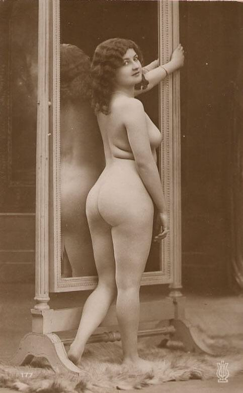 Nude woman standing next to a full length mirror