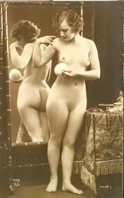 Nude woman standing holding a powder puff. A mirror is behind her