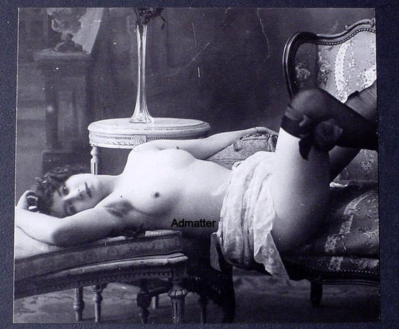 flapper reclining topless on a sofa, while wearing black stockings