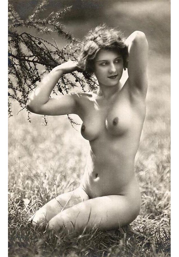 Nude woman kneeling outside next to a tree. Circa 1920s