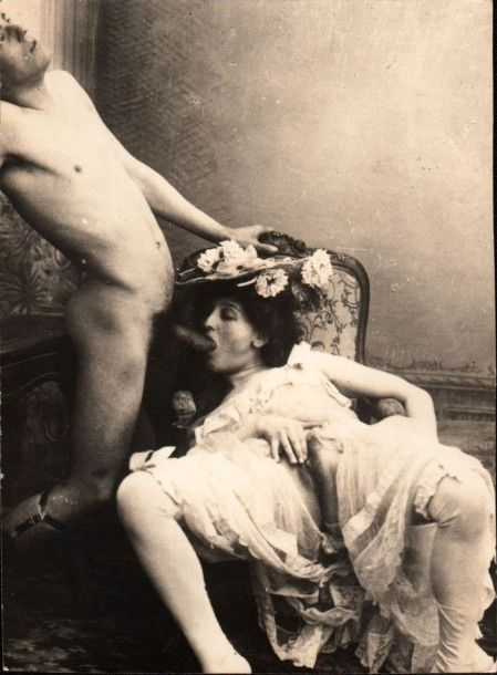 Woman in flowered hat performing fellatio on a standing man. Victorian.