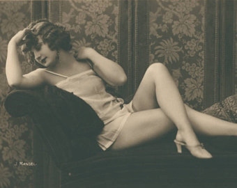Image of  a flapper in a white chemise and high heeled shoes.