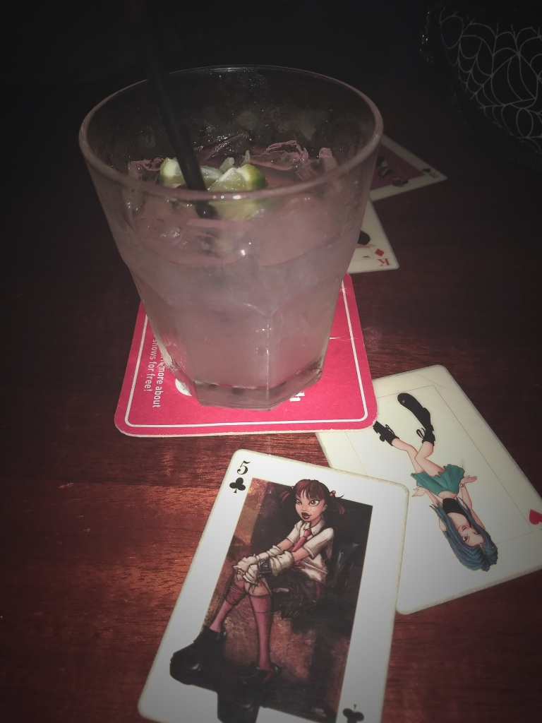 A pink drink on a table top with playing cards featuring cartoon women
