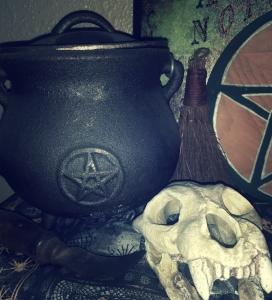 An iron cauldron, a curved knife, an animal skull, and a hand broom