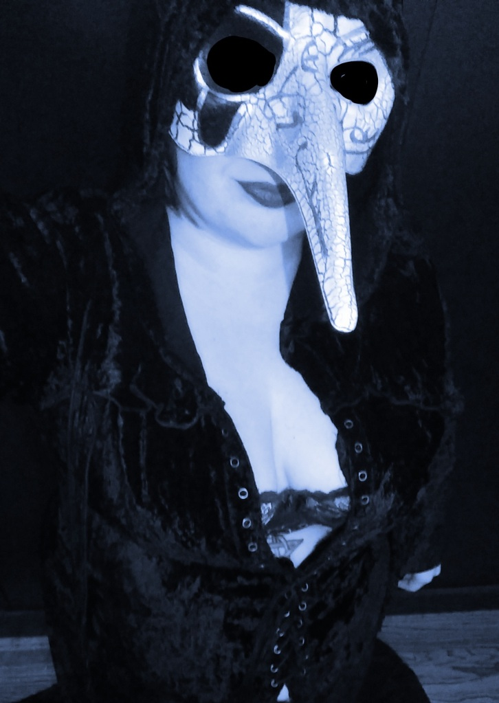 Lucy in a plague mask and black cloak with a lace bra and deep cleavage