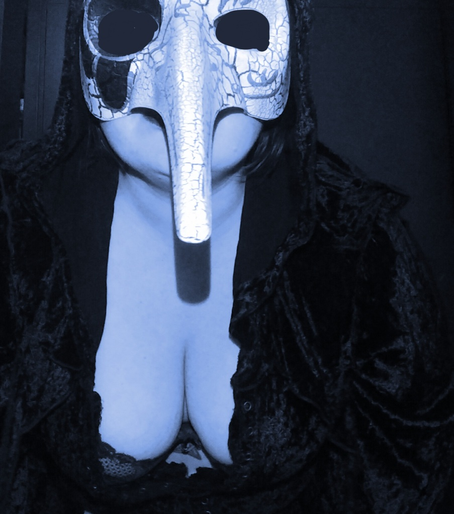 Lucy in a plague mask, crawling in a cloak and lace bra