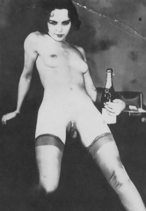 Nude flapper, facing the camera, wearing stockings and holding a champagne bottle