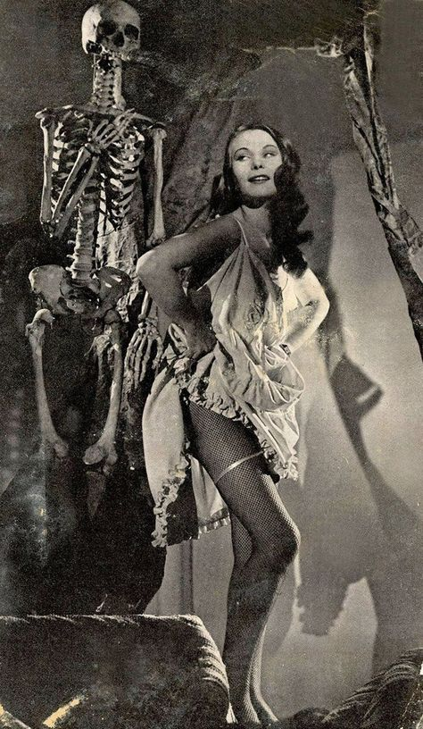 vintage photo of a women in a nightgown with a skeleton