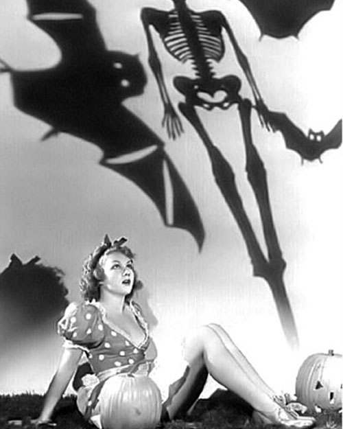 1940s pinup with a jack-o-lantern and shadow skeletons