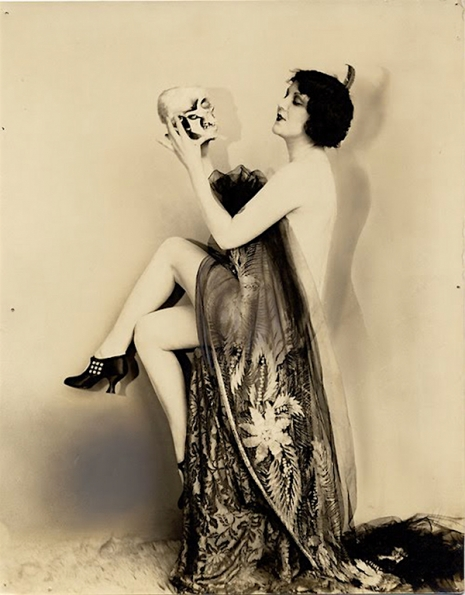 flapper wearing a sheet and devil horns holding a skull