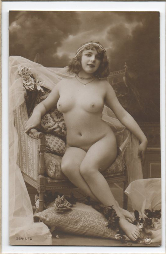 vintage boudoir postcard. Nude woman seated on a chair surrounded by flower