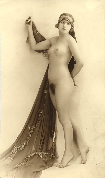 Vintage photo of a nude woman wearing a headwrap and holding a veil