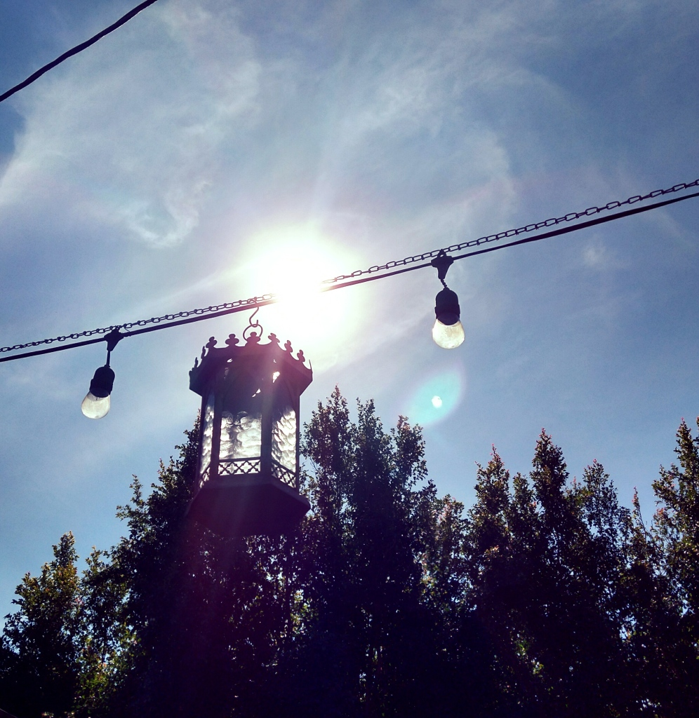 A lantern with a crenellated top hanging on a wire with the sun behind it